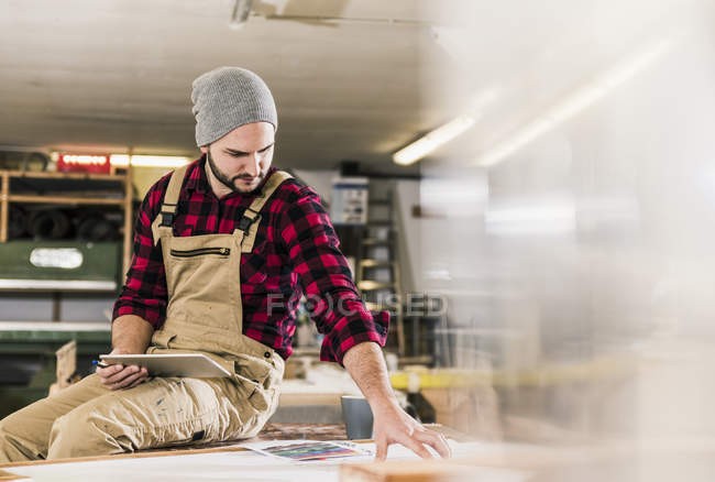 Worker with tablet looking at draft in workshop — Stock Photo