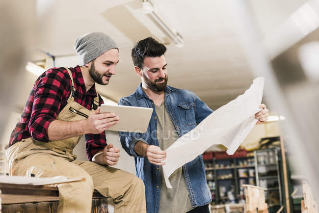 Two men with tablet looking at draft in workshop — Stock Photo
