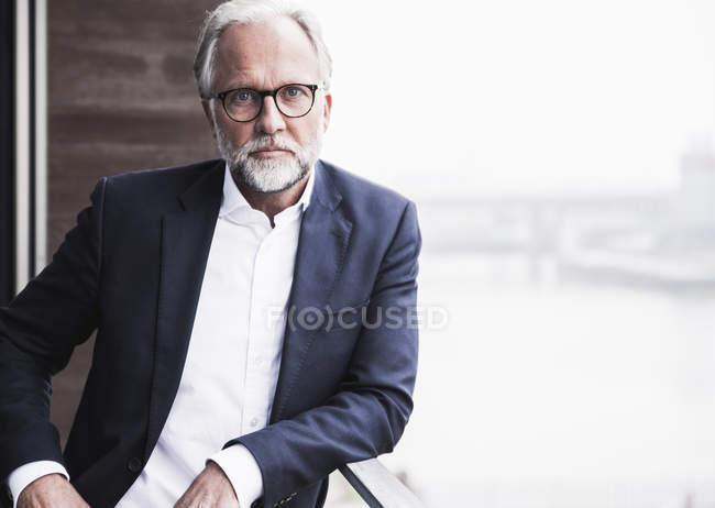 Retrato de empresario maduro de pie en el balcón - foto de stock