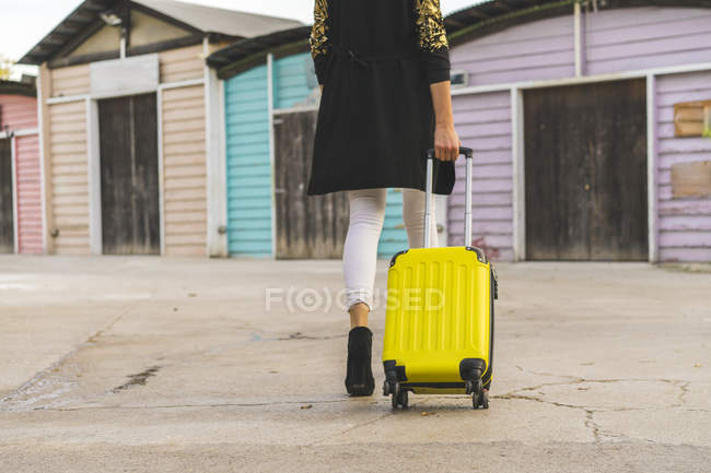 Cropped image of woman walking with yellow travel bag on street — Stock Photo
