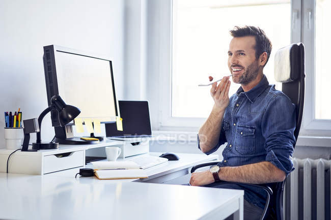Smiling man using smartphone at desk in office — Stock Photo