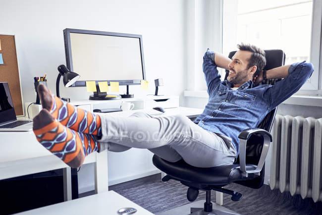Розслаблена людина сидячи на столі в офісі і дивлячись на екрані комп'ютера — стокове фото