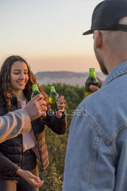 Happy friends clinking beer bottles outdoors at sunset — Stock Photo