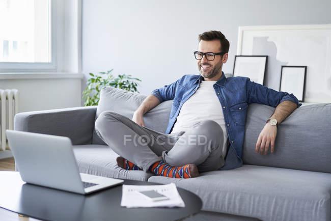 Homme souriant détendu assis sur le canapé et regardant ordinateur portable — Photo de stock