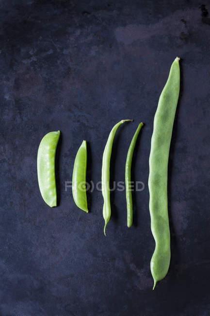 Verschiedene Arten von Bohnen und Erbsen auf dunklem Metall — Stockfoto