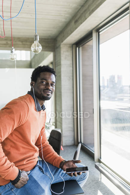 Portrait of smiling casual businessman with earphones and smartphone — Stock Photo