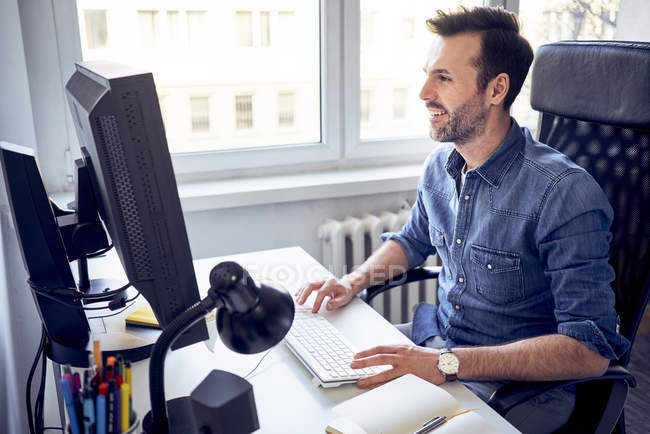 Smiling man working on computer at desk in office — Stock Photo