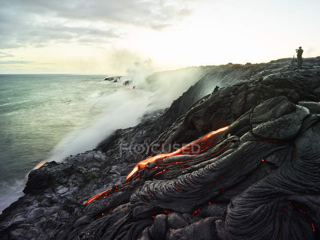 Hawaii, Big Island, Hawai'i Volcanoes National Park, lava flowing into pacific ocean, photographer — Stock Photo