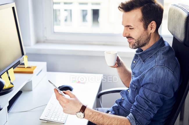 Homem sorridente olhando para o celular e bebendo café na mesa no escritório — Fotografia de Stock