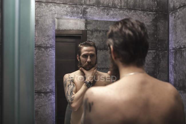Портрет бородатого людини дивлячись на його дзеркальному зображенні — стокове фото