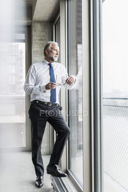 Seriöser reifer Geschäftsmann, der am Fenster steht und hinausschaut — Stockfoto