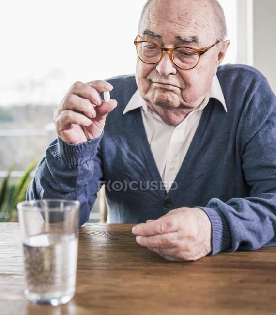 Verticale d'homme aîné s'asseyant à la table avec la pillule et le verre de l'eau — Photo de stock
