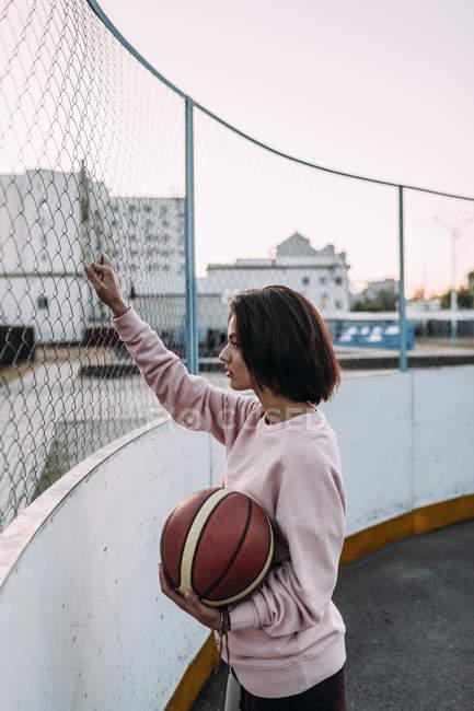 Молодая женщина, стоящая с баскетбольным мячом возле забора — стоковое фото