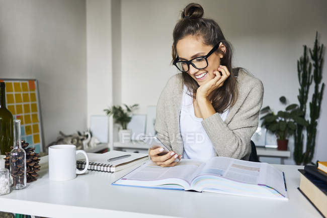 Happy female student learning at home, checking messages on her phone — Stock Photo