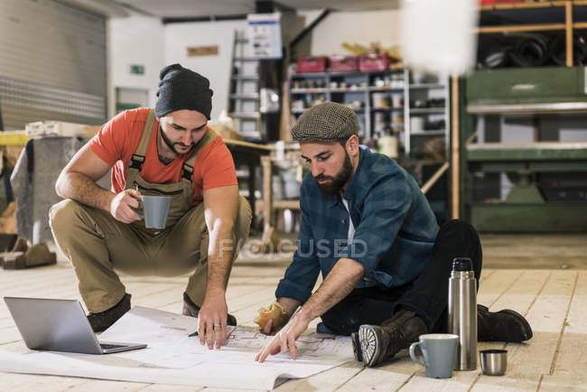 Two men with laptop looking at construction plan on the floor — Stock Photo