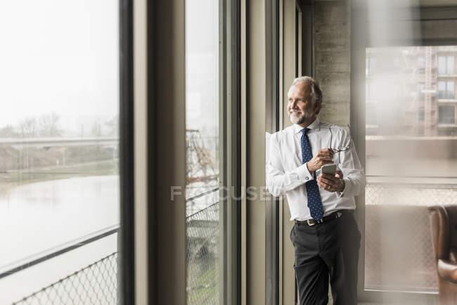 Sorridente uomo d'affari maturo in piedi alla finestra e guardando fuori — Foto stock