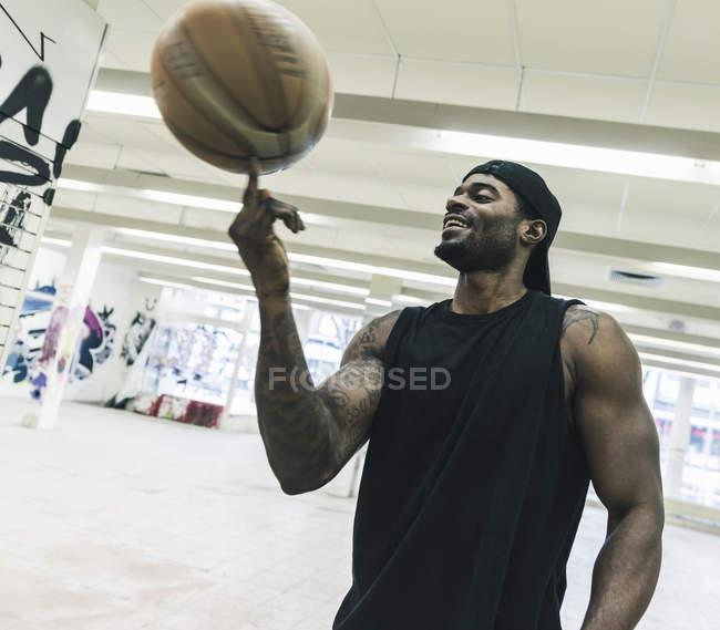 Улыбающийся африканский американец с татуировками, балансирующий баскетбольный мяч на пальце — стоковое фото