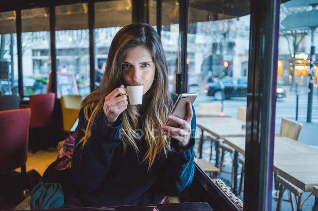 Paris, France, portrait of young woman with smartphone drinking espresso in a coffee shop — Stock Photo