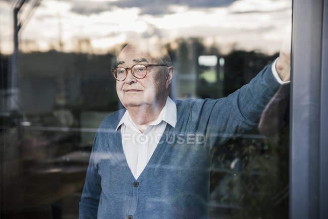 Verticale de l'homme sérieux à la fenêtre regardant dehors — Photo de stock
