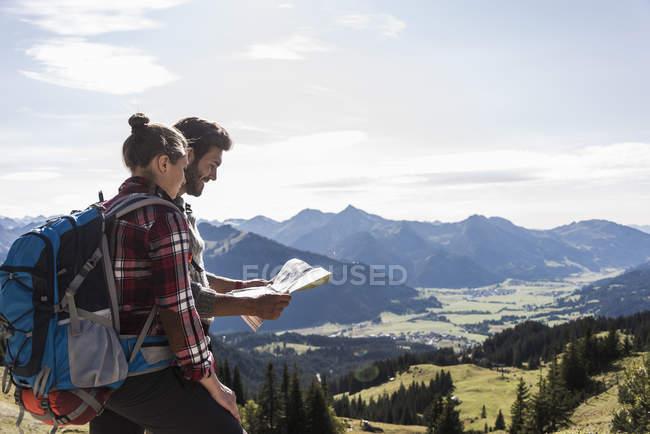 Austria, Tirolo, giovane coppia che guarda la mappa del paesaggio montano — Foto stock