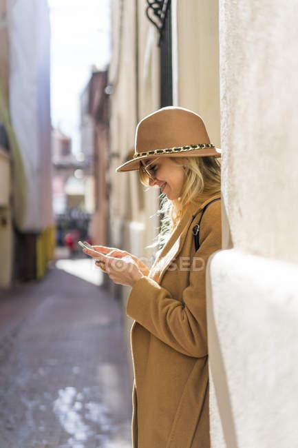 Модна молода жінка на смузі за допомогою мобільного телефону — стокове фото