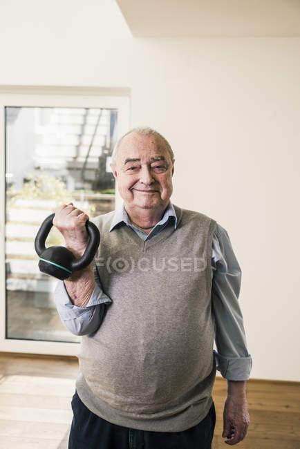 Verticale d'homme aîné de sourire faisant un exercice de poids — Photo de stock
