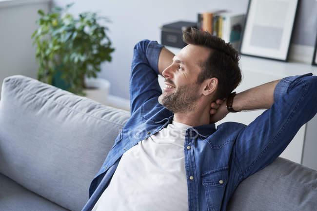 Улыбающийся расслабленный мужчина сидит на диване и смотрит в сторону — стоковое фото