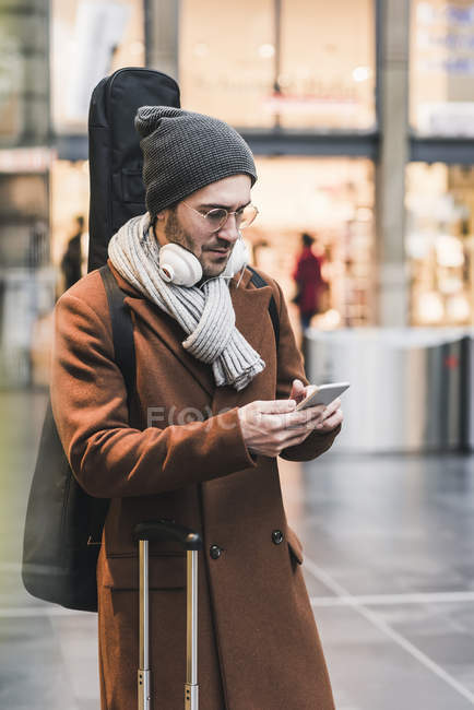 Young man with guitar case using cell phone — Foto stock