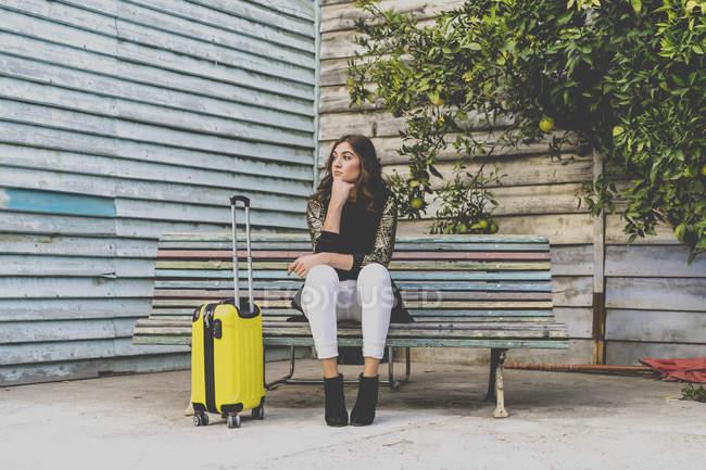 Mujer joven con bolsa de viaje esperando en el banco - foto de stock