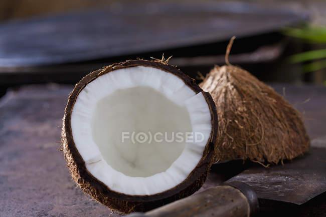 Свежий пополам кокос овый на размытом фоне с ржавым ножом — стоковое фото