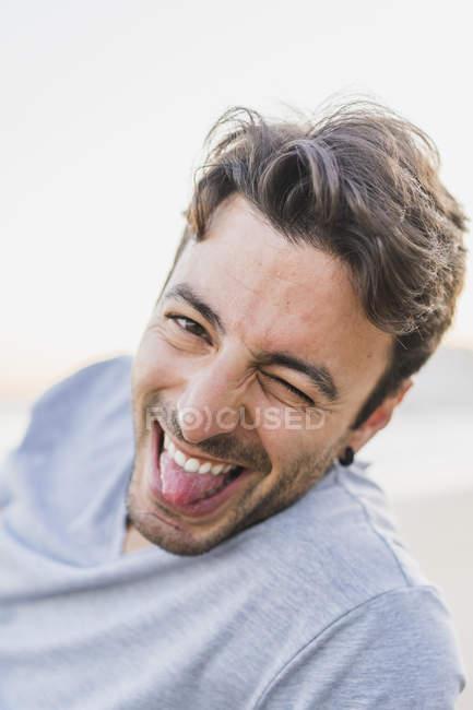 Porträt eines augenzwinkernden jungen Mannes, der die Zunge heraushält — Stockfoto