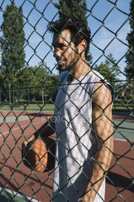 Человек с баскетбольным мячом за проволочной сеткой — стоковое фото