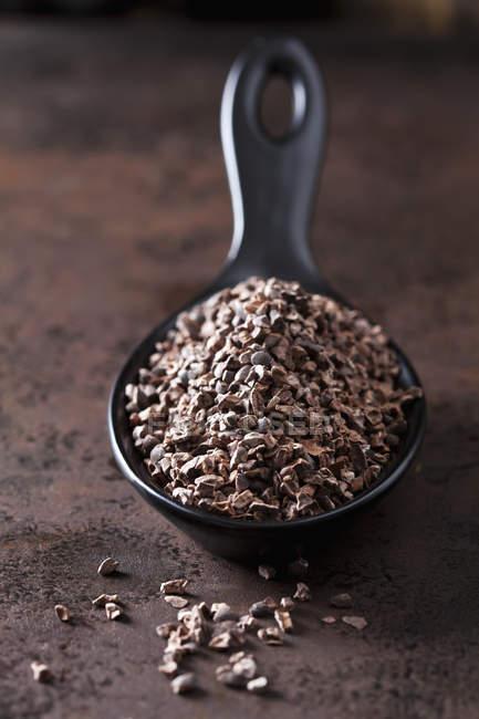 Cuchara de puntas de cacao crudas trituradas sobre metal oxidado - foto de stock
