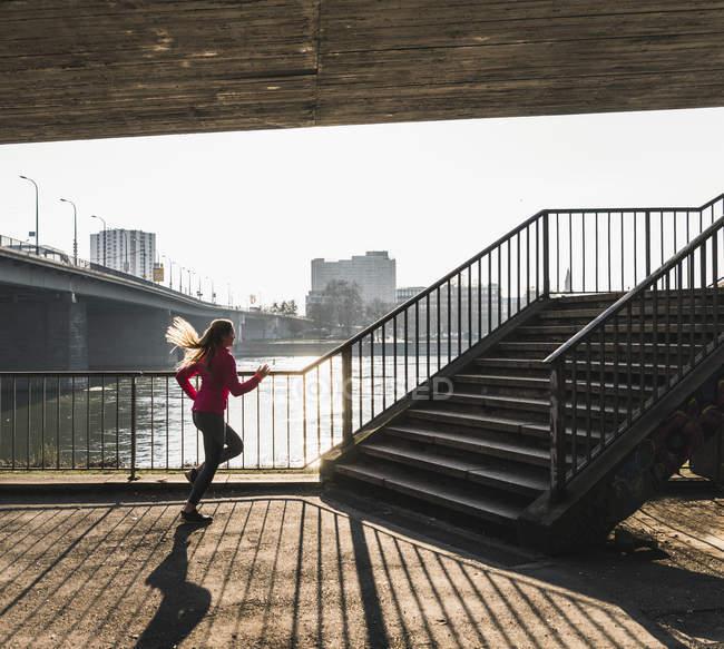 Молодая женщина бежит к лестнице у реки — стоковое фото