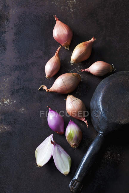 Fresh whole and halved onions on dark grunge background with old pan — Stock Photo