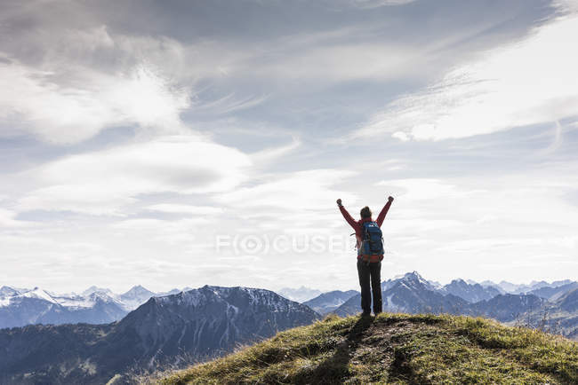 Austria, Tyrol, young woman standing in mountainscape and cheering — Stock Photo