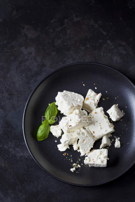 Feta, herbes and basil leaves on black plate — Stock Photo