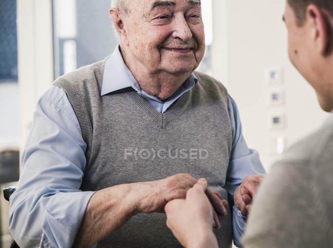 Homem sênior sorrindo para o jovem segurando as mãos — Fotografia de Stock