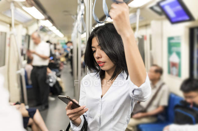 Businesswoman using cell phone in the subway — Stock Photo