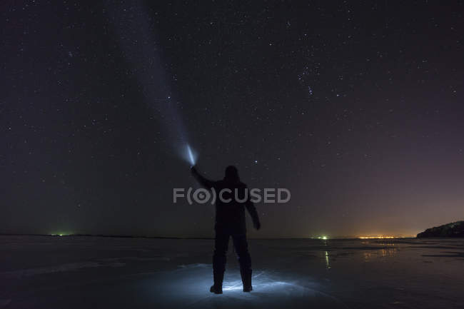 Russia, Amur Oblast, silhouette of man with blue ray standing on frozen Zeya River at night under starry sky — Stock Photo