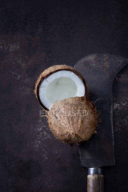 Fresh halved coconut with rustic knife on dark grunge background — Stock Photo