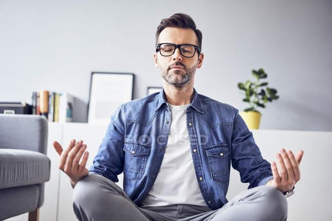 Расслабленный человек, медитирующий дома — стоковое фото