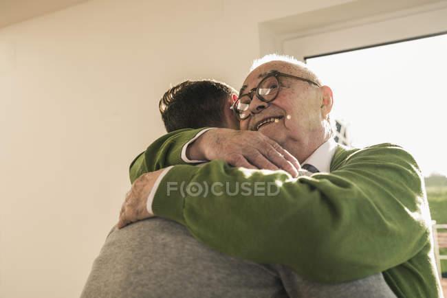 Homme aîné de sourire étreignant le jeune homme — Photo de stock