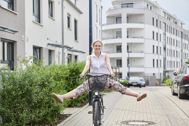 Happy young woman riding bicycle in housing area — Stock Photo