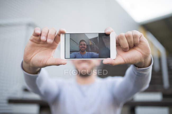 Smiling man taking selfie with cell phone, close-up — Stock Photo