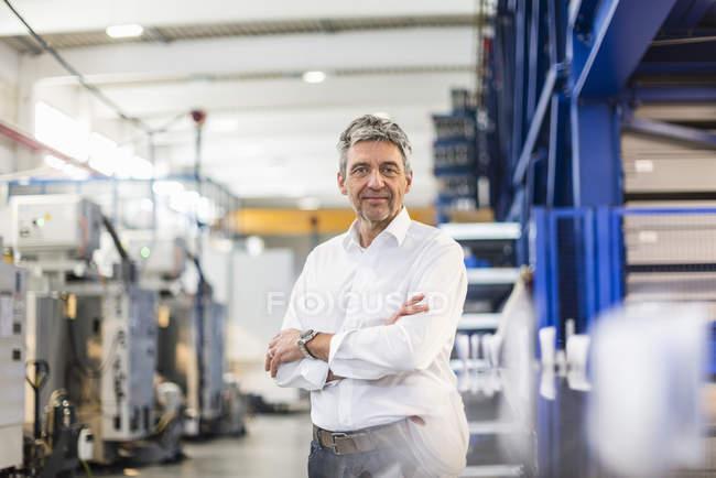 Усміхнений бізнесмен у виробничій залі — стокове фото
