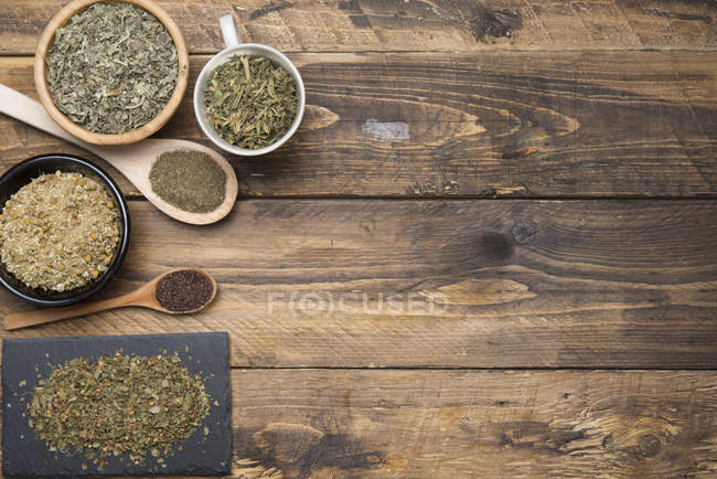 Top view of chamomile, mint, thyme, green tea on wooden table — Stock Photo