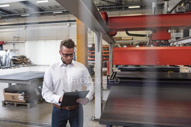Mann schreibt auf Klemmbrett in Fabrikhalle — Stockfoto