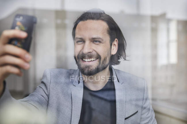 Retrato de hombre de negocios guapo barbudo en la ventana y tomar foto selfie en el teléfono móvil - foto de stock