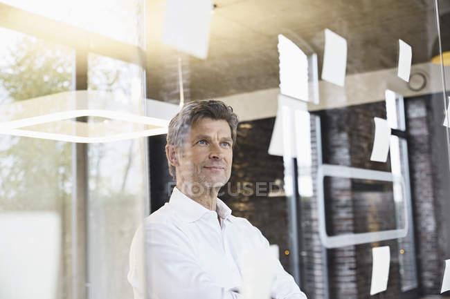 Reifer Geschäftsmann blickt im Büro auf klebrige Zettel an Glasscheibe — Stockfoto